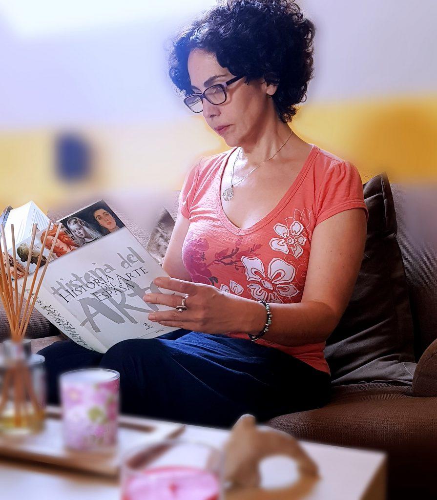 Nedda Soriano sentada con su libro de historia del arte entre la manos